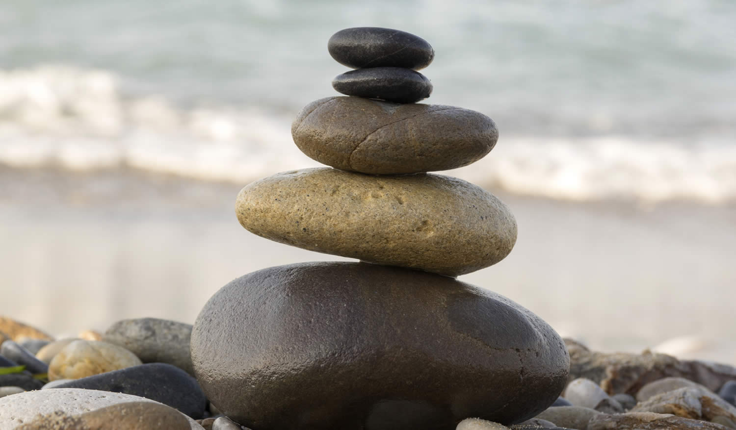 smoothed stones stacked atop one another, at the beach, a symbol of alignment, balance and peacefulness